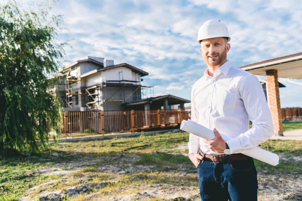 man standing in front yard of house